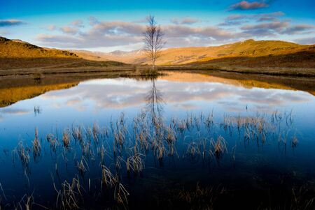 blue skies and hills reflecting in pond in the lake district Stock Photo - 19435743