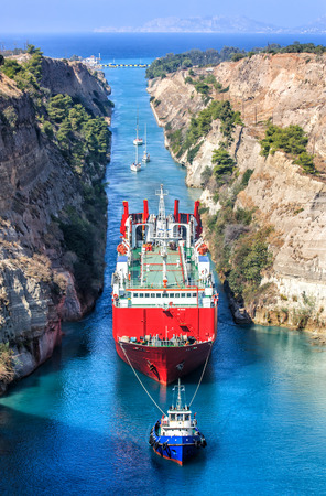 A tug boat pulling a freight ship though the Corinth Canal, Greece