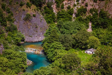 Vikos Gorge, House in the forest near the blue river