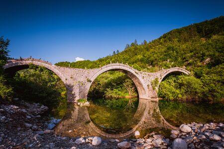 Arches stone bridge of Kalogeriko on the river of Voidomatis. Central Zagoria, Epirus, Greece.