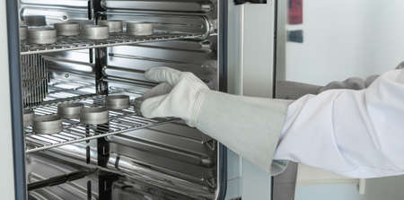 A gloved lab technician removes hot sample bottles from the drying chamber. Foto de archivo