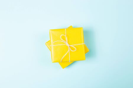 Two yellow packed square gift boxes on pastel blue background. Flat lay. Minimal style. Holiday concept.