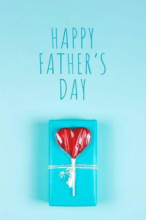 Blue gift box decorated with heart shaped red lollipop on light blue background. Happy Fathers day greeting card