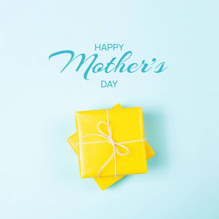 Happy mothers day greeting card. Yellow square gift boxes on blue background. Flat lay. Banco de Imagens