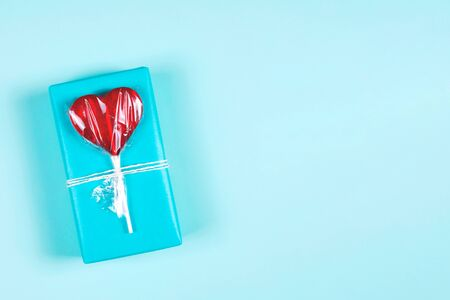 Festive background. Blue gift box decorated with red heart shaped lollipop. Flat lay style, copy space Banco de Imagens