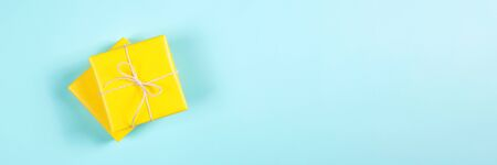 Two yellow gift boxes on blue background. Banner for website