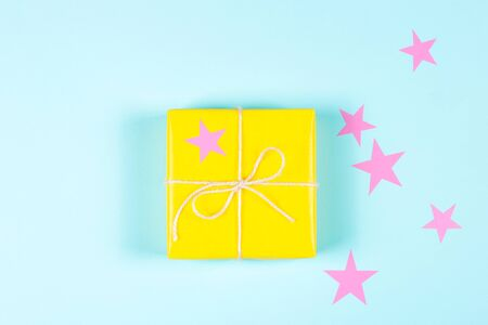 Yellow packed gift box on blue background with pink stars. Flat lay. Holiday concept. Banco de Imagens