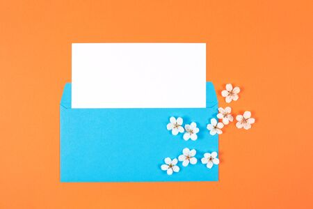 Blue envelope with white card and flowers on orange background. Top view. Copy space