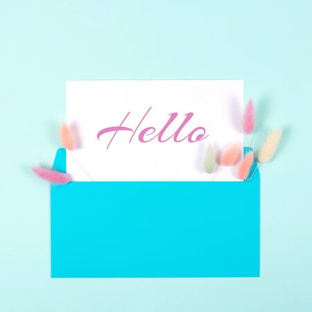 Square hello card with blue envelope and colorful spikelets on pastel blue background. Flat lay style. Greeting concept