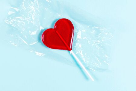Red heart shaped lollipop on transparent packaging and blue background. Top view