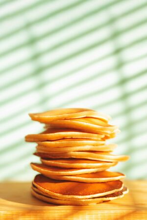 Stack of tasty pancakes on wooden dish and shadow background. Hard light. Soft selective focus. Home cooking concept. Banco de Imagens