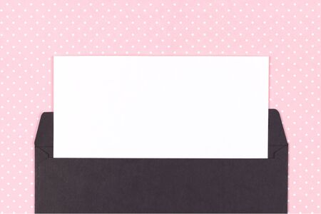 Black envelope with white card on pink dotted background. Mockup. Top view.
