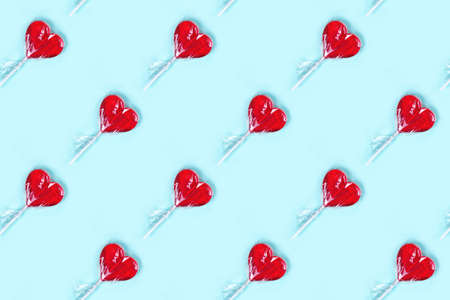 Cute candy pattern made with red heart lollipop on blue background. Romantic concept Banco de Imagens