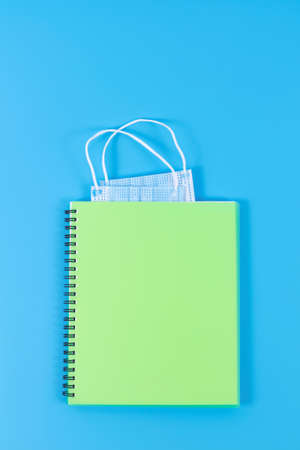Light green copybook with two blue face masks as bookmark on blue background. Minimal style. Top view. Post-pandemic life concept. Banco de Imagens