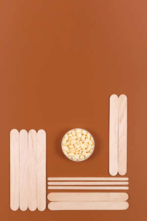 Depilation vertical background. Wooden spatulas and jar with natural granular wax on brown backdrop. The concept of skincare, waxing. Flat lay style Banco de Imagens
