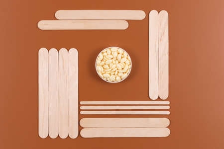 Monochrome background made with natural hot granular wax and wooden spatulas on brown backdrop. Flat lay style. Depilation, sugaring, waxing concept.