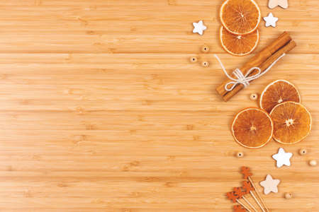 Bakery background made with dried orange slices, decorations and cinnamon sticks on wooden table. Top view. Cooking at home concept