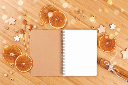 Christmas bakery background with open blank notebook, dried orange slices, cinnamon sticks and wooden decorations. Flat lay style. Copy space