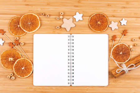 Open notepad decorated with stars, beads, dried orange slices, wooden gingerbread men and cinnamon sticks. Flat lay style. Copy space. Baking concept