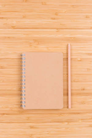 Closed blank spiral notepad and pencil on bamboo table. Eco friendly workplace. Top view. Minimal style