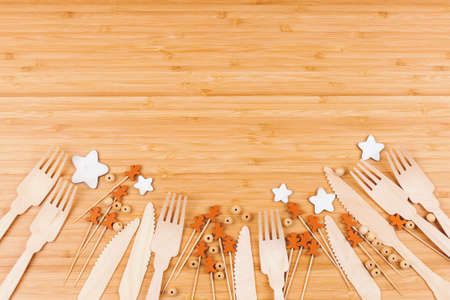 Bamboo table surface decorated with wooden disposable forks, knifes and seasonal elements. Top view.