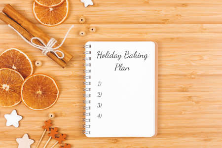 Spiral notebook on wooden background decorated with stars, beads, cinnamon sticks and orange dried slices. Holiday baking plan. Flat lay style Banco de Imagens