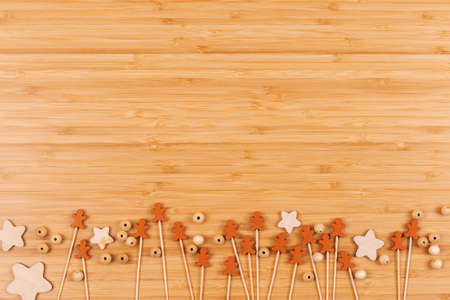 Wooden background with decorative gingerbread men, stars and beads on table. Holiday baking concept. Copy space Banco de Imagens