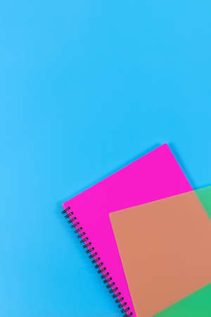 Geometric vertical background. Magenta spiral copybook and transparent green cover on blue backdrop. Top view. Copy space Banco de Imagens