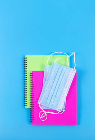 Two spiral copybooks with face masks on blue background. Top view. New normal concept.