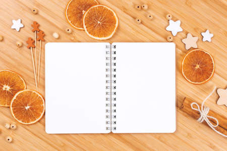 Open notepad, dried orange slices, stars, beads, wooden gingerbread men and cinnamon sticks on bamboo table. Cooking concept. Flat lay style, copy space