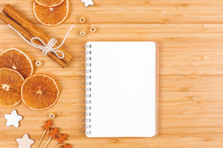 Open blank notepad on bamboo table with winter season decorations. Flat lay. Place for text. Banco de Imagens