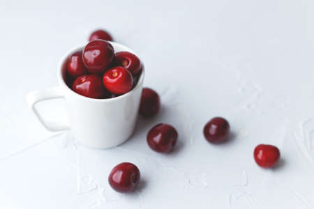 White cup full of juicy vinous cherries on pastel blue concrete background. Shot at angle. Soft selective focus