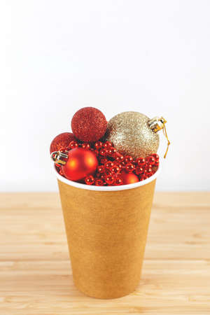 Cardboard cup with New Year decorations on bamboo table and white background. Close-up, copy space