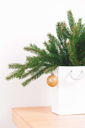 Christmas tree branch with golden bauble in white shopping bag. Side view. Holiday preparation concept. Banco de Imagens