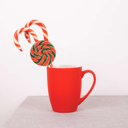 Red cup with Christmas treats. Candy canes and lollipop. Front view, place for text
