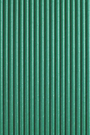 Green paper straws as background. Top view