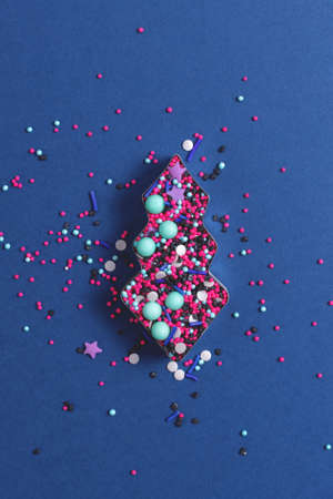 Edible confetti and cupcake sprinkles in metal pastry cutter on deep blue background. Top view. Banco de Imagens
