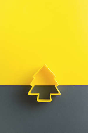 Color of year 2021. Christmas tree pastry cutter on yellow and gray background. Top view. Copy space