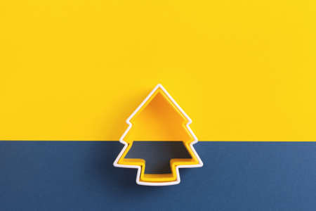 Christmas tree pastry cutters on yellow and blue background. Top view. Copy space.