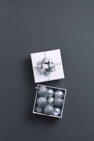 Open giftbox with silver Christmas tree metallic decorations on gray background. Top view, copy space. Banco de Imagens