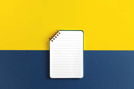 Blank ruled notepad on yellow and blue background. Top view, copy space. Banco de Imagens