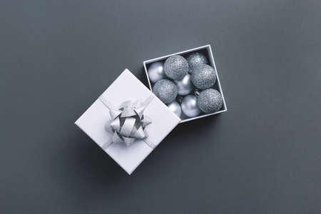 Grey and silver Christmas baubles in white wrapped square gift box on gray background. Top view.
