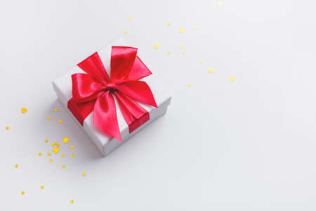 White gift box with red bow and golden glitter on white background. Top view. Copy space.