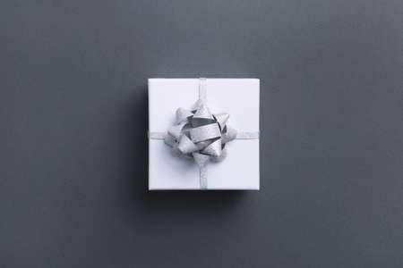 White square gift box with silver bow on gray background. Top view.