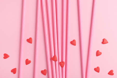 Valentines day background made of pink drinking paper straws and edible sweet hearts on pink backdrop. Top view.