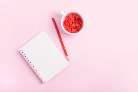 Valentines day concept. White notebook page, pencil and red sweet heart decorations on pastel pink background. Flat lay style, copy space. Banco de Imagens