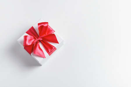 White present box tied with red beautiful bow on white background. Top view, copy space.