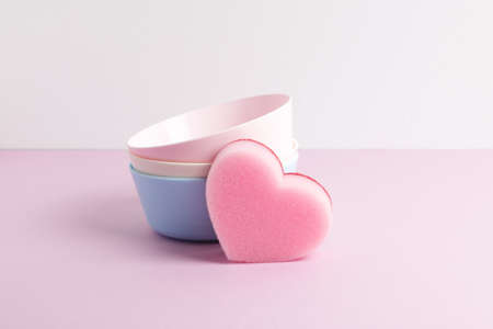 Front view of clean colourful bowls and pink heart shaped sponge. Dishwashing concept.