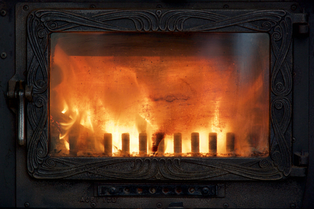 stove pipe: Oven fire behind the oven door of historical woodstove Stock Photo