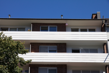 hotel exterior: Residential apartment or hotel exterior from street level view. Tree in foreground with blue sky background